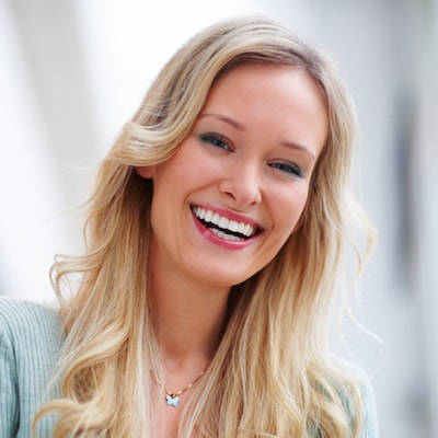 An attractive woman with long blonde hair smiling and laughing because of the cosmetic dentistry services offered by Dr. Stephen Maloney and Fireweed Dentistry in Anchorage