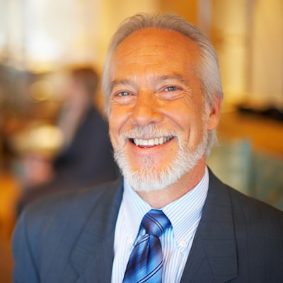 An older gentleman with gray hair and a neatly trimmed beard, smiling in a dark blue suit and tie to show that Dr. Stephen Maloney offers Restorative Dentistry services in Anchorage