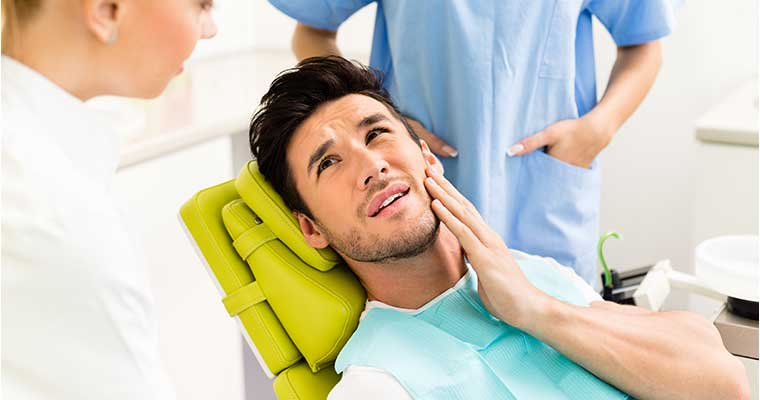 Young man in dental chair holding his jaw while suffering from one of the types of dental emergencies.